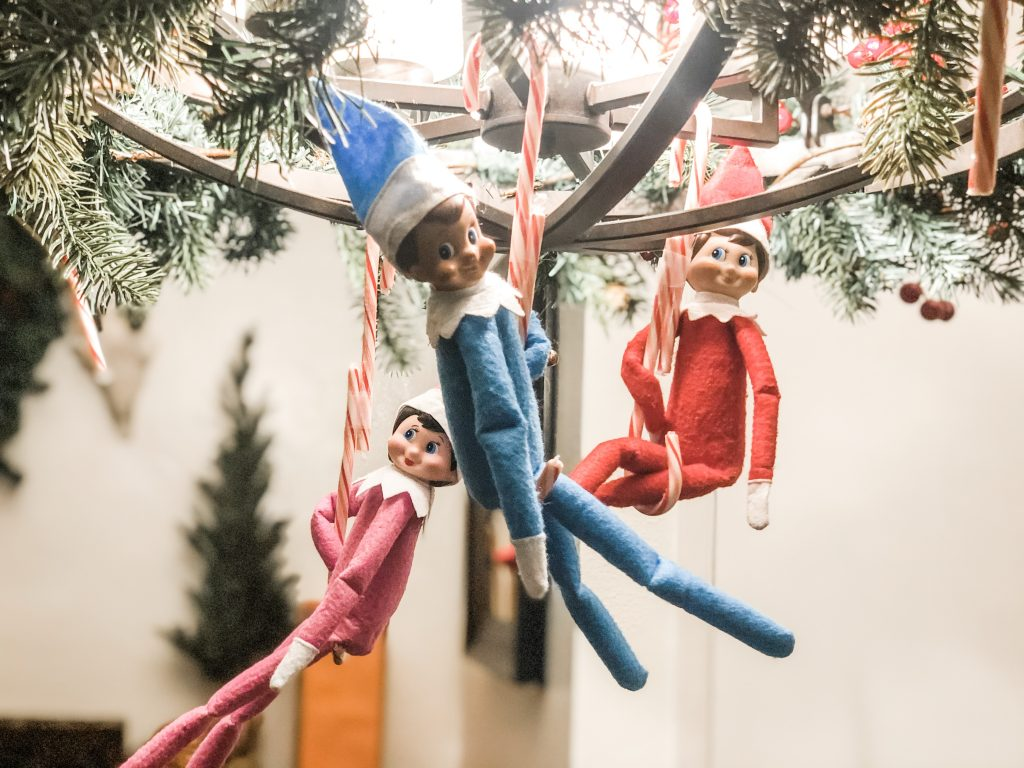 Elf on the Shelf swinging from candy canes