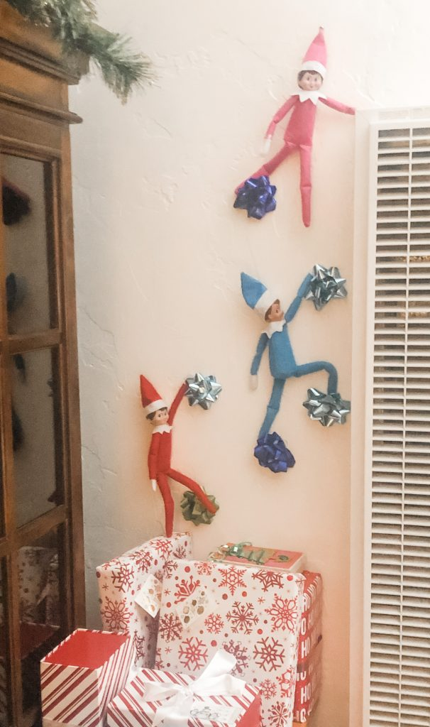 Elf on the shelf climbing up wall on bows
